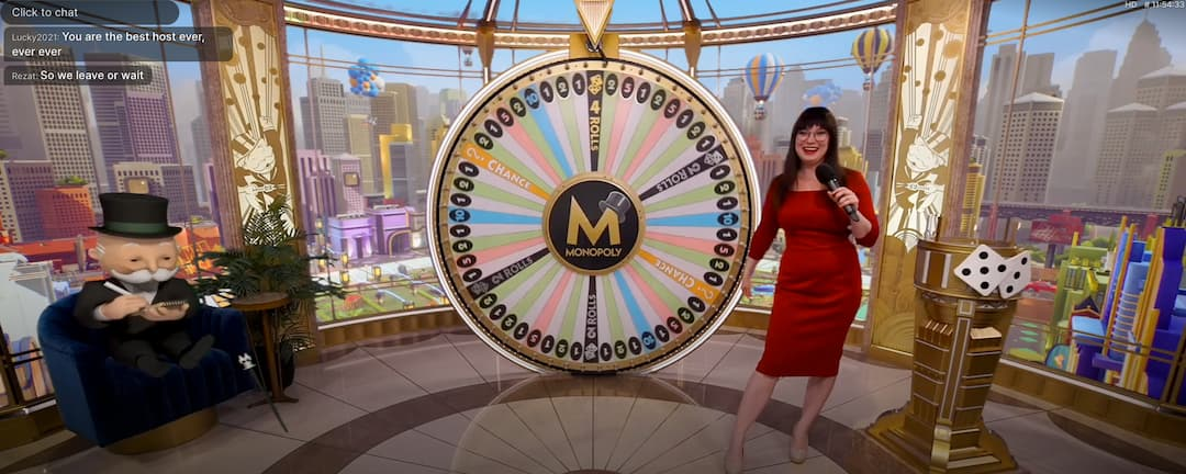 smiling Woman dressed in red with the Live monopoly wheel and Mr Monopoly taking notes
